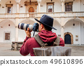 Man with professiona camera and hat with backpack 49610896