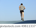 Back view of a jogger man running against blue sky 49611337