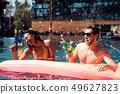 Young Smiling Couple having Fun in Swimming Pool 49627823