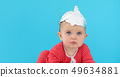 Baby in a foil hat sits on a blue background 49634881