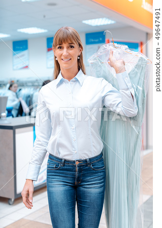 Woman customer getting clean clothes back from the textile cleaning 49647491