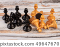 Group of chess pawns on wooden background. 49647670