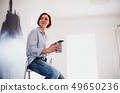 A portrait of young woman painting wall black. A startup of small business. 49650236