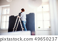 A young woman painting wall black. A startup of small business. 49650237