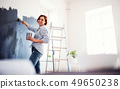 A portrait of young woman painting wall black. A startup of small business. 49650238