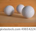 Golf ball on the wood floor. 49654224