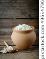 Cottage cheese in brown rustic clay pot and spoon. 49654796