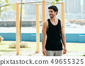 Portrait of Male Personal Trainer Working Out In City Park 49655325