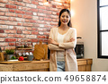 woman standing with arms crossed against kitchen 49658874