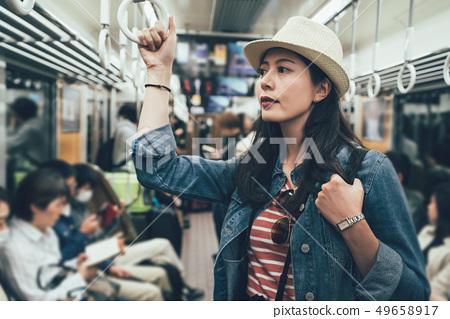 woman taking metro standing holding handle 49658917