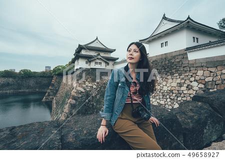 photographer sitting on bridge with river 49658927