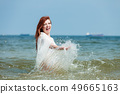 Girl splashing water on the coast. 49665163
