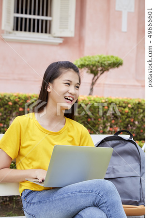 woman using a laptop computer in a park 49666601