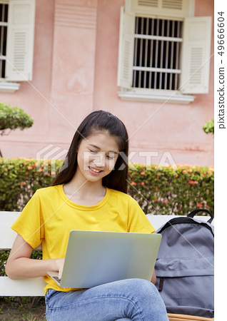 woman using a laptop computer in a park 49666604