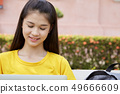woman using a laptop computer in a park 49666609
