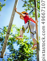 Little brave caucasian girl at outdoor treetop climbing adventure park 49667107
