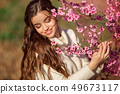Portrait of young beautiful girl with perfect skin posing near blossom tree in cherry garden 49673117