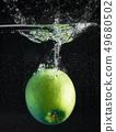 fresh apple falling in water 49680502
