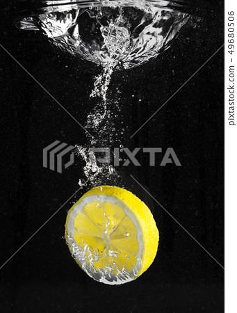 fresh lemon falling in water 49680506