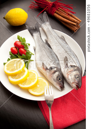 isolated fresh bass dish in stone background 49681056