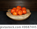 Pile of tangerines in a wooden bowl  49687445
