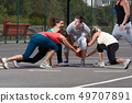 Young people playing basketball on a playground 49707891