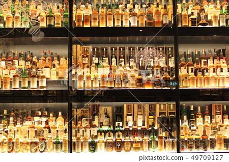 Whiskey bottles lined up on shelves 49709127