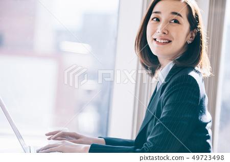 老闆女人在靠窗的座位上前往電腦 49723498