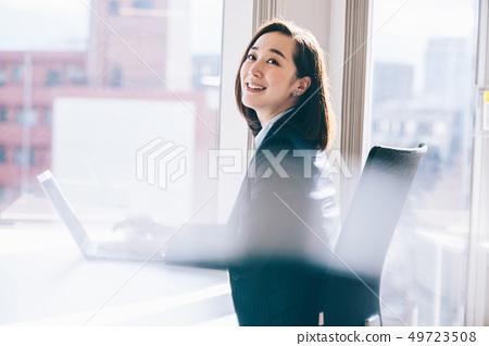 老闆女人在靠窗的座位上前往電腦 49723508