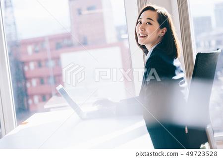 창가의 자리에서 컴퓨터로 향하는 보스의 여자 49723528