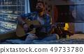 Man taking notes and playing guitar 49733780