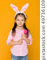 cute little girl with Easter bunny ears holding colorful eggs 49736109