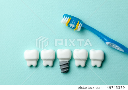 Healthy white teeth and implants on green mint background with toothbrush 49743379