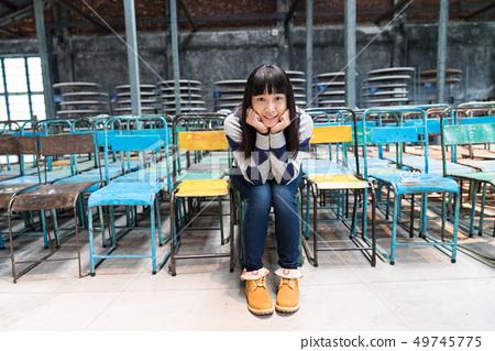 一個可愛的小女孩坐在一把令人困惑的椅子上。本地信息是個人獨特的。 49745775