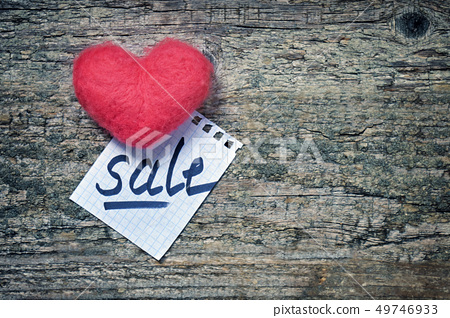 Pink wool toy heart lying with a notepad sheet with a word sale written on it on a wooden desk 49746933
