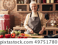 Cheerful senior woman cutting vegetables for salad 49751780