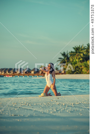 beautiful young woman posing on white beach 49751878
