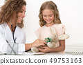Woman pediatrician examining girl's toy in clinic 49753163