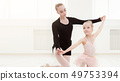 Little girl looking at professional ballet dancer 49753394