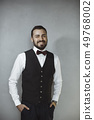 Smiling man in black vest and bow tie 49768002