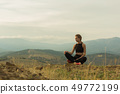 young beautiful girl sitting in mountains 49772199