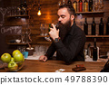 Young tattooed bartender with great beard tasting a glass of wine. 49788390