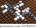 playing stones on wooden board in Go 49789047