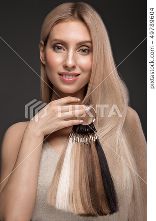 Beautiful blond girl with a perfectly smooth hair, classic make up with a palette for hair 49789604