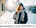 Happy young woman wearing warm scarf and hat 49790711