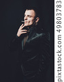 a young man smokes a cigarette, a black background, a classic black suit 49803783