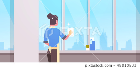 woman in gloves and apron cleaning windows with rag cleaner spray rear view housewife doing 49810833