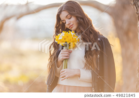Portrait of smiling teenager girl are holding bouquet of narcissus flowers in park over sunset 49821845