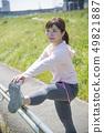 ผู้หญิงกำลังยืดกีฬากลางแจ้ง 49821887
