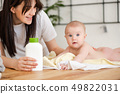 Mother with lotion in hand and look at baby 49822031